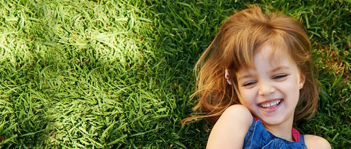 Child plays on a healthy lawn. Trust TruGreen with your lawn care.